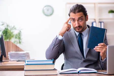 Young male businessman reading books at workplace Foto de archivo
