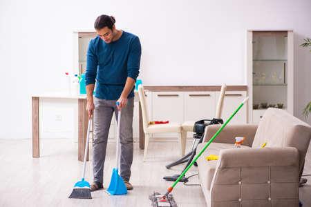 Young man husband doing housework at home Banco de Imagens