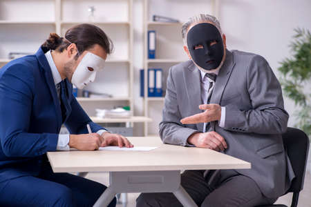 Two businessmen wearing masks during negotiations