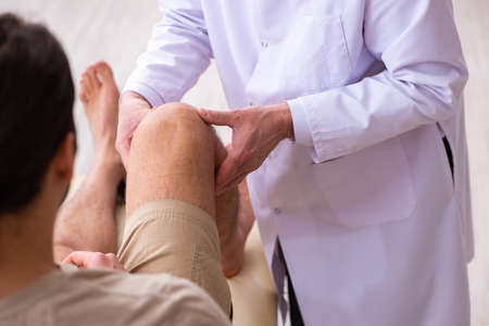 Experienced doctor traumatologist examining young male patient Standard-Bild