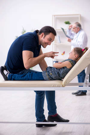Young father and his daughter visiting old male doctor