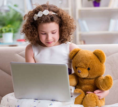Little girl surfing internet on laptop
