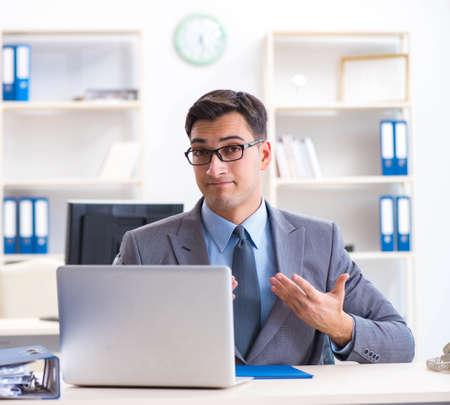Handsome businessman employee sitting at his desk in office Banco de Imagens