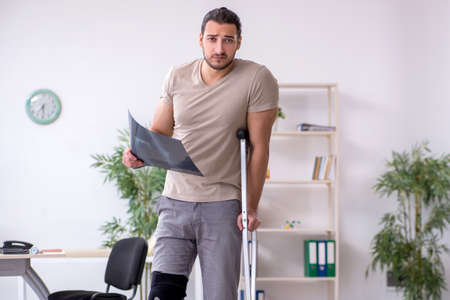Young leg injured man with crutches looking x-ray