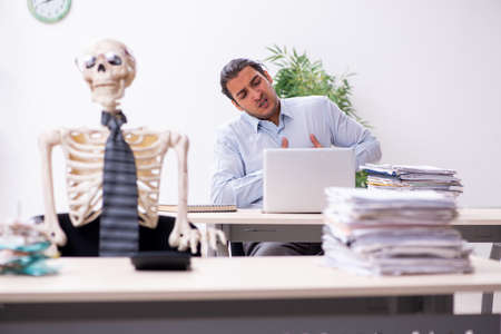 Young male employee and skeleton in the office