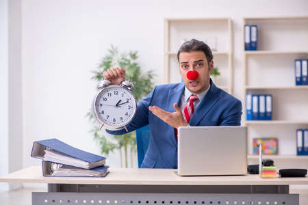 Funny employee clown working in the office