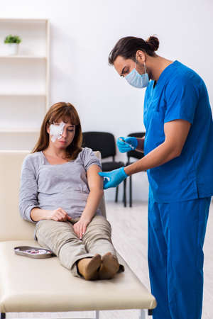 Young head injured woman visiting young male doctor Stock Photo