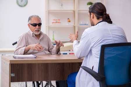 Old blind man visiting young male doctor