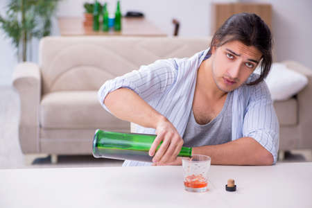 Young male alcoholic drinking whiskey at home Banque d'images