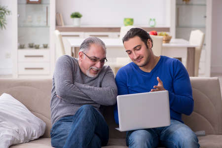 Father and son sitting on the sofa with computer