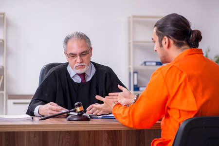 Old male judge meeting with young captive in courthouse 写真素材