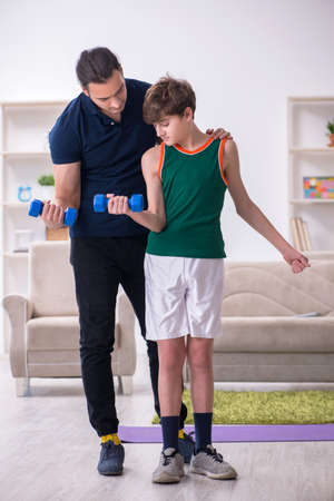 Father and son doing sport exercises indoors