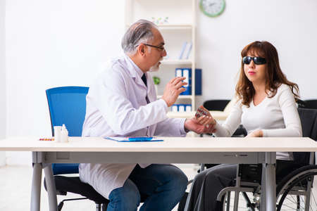 Young woman visiting old male doctor ophthalmologist