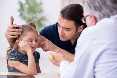 Young father and his daughter visiting old male doctor Imagens