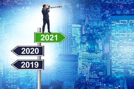 Road sign and businessman with 2020 and 2021