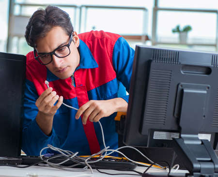 Computer repairman working on repairing computer in IT workshop Stock fotó