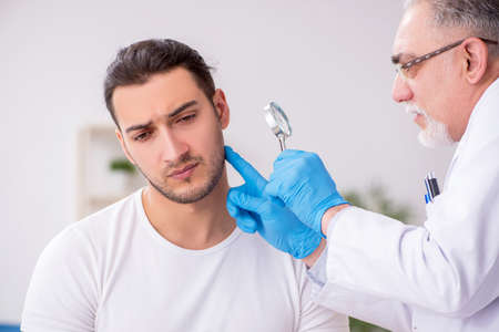 Young man visiting experienced doctor dermatologist