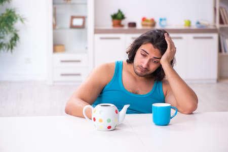 Young man waking up at home Фото со стока