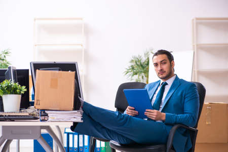 Young male employee in moving concept Stock Photo