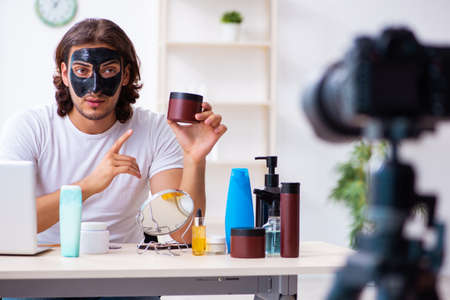 Young male cosmetician recording video for his blog 免版税图像