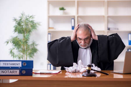 Old male judge working in courthouse