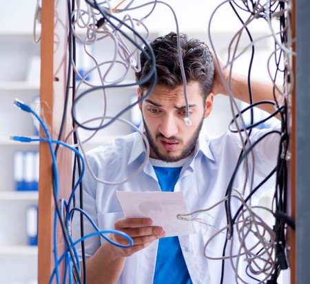 Computer repairman working on repairing network in IT workshop Banque d'images