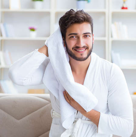 The young man in a bathrobe after shower drying hair with a towe Banque d'images