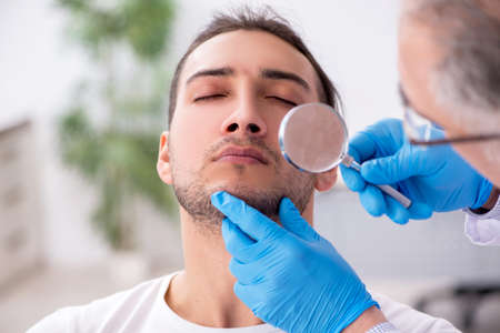 Young man visiting experienced doctor dermatologist Standard-Bild