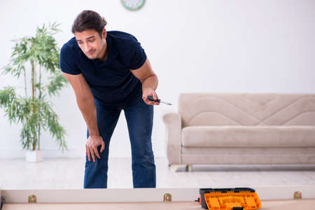 Young male contractor installing furniture at home