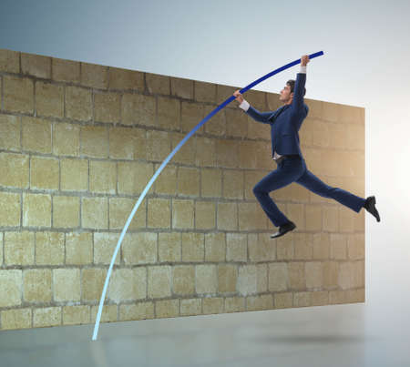 The businessman jumping over brickwall in business concept