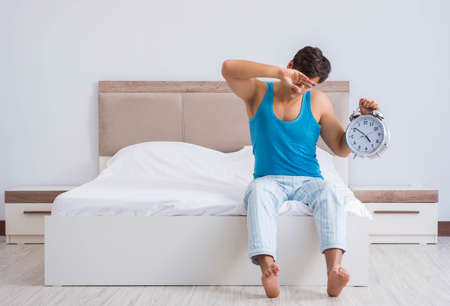 The young man waking up in bed