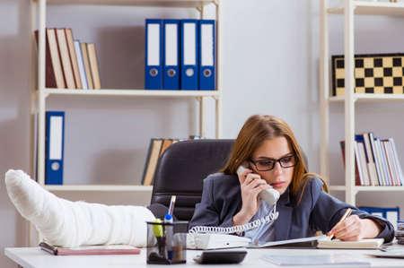 Businesswoman employee with broken leg in office