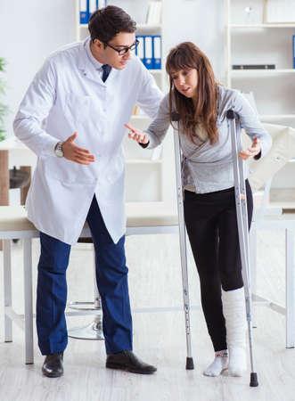 Doctor examining patient with broken leg