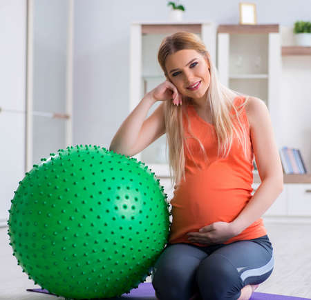 Young woman preparing for birth exercising at home Reklamní fotografie