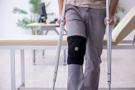 Young leg injured man with crutches