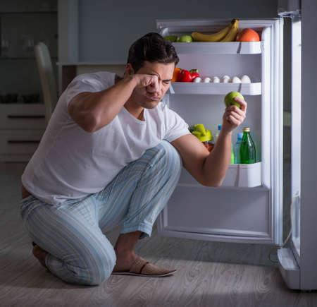 Man at the fridge eating at night