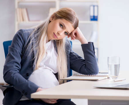 Pregnant woman employee in the office