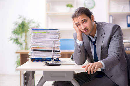 Young male businessman unhappy with excessive work