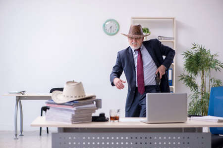 Funny old boss in cowboy hat in the office