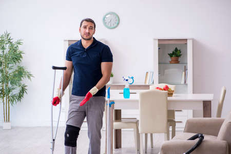 Young leg injured contractor cleaning the house Stock fotó