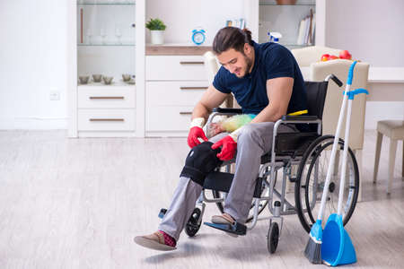 Young leg injured contractor in wheel-chair cleaning the house