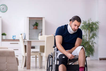 Young leg injured man in wheel-chair suffering at home