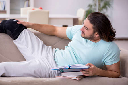 Young leg injured student studying at home Stock fotó