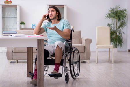 Young student in wheel-chair studying at home