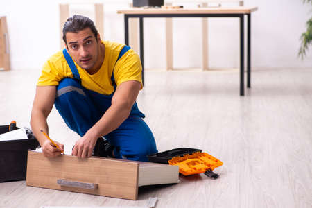Young male carpenter working indoors