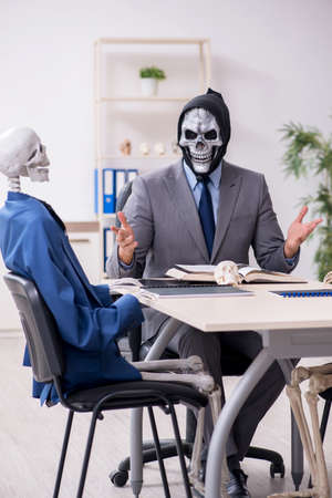 Funny business meeting with devil and skeletons 写真素材