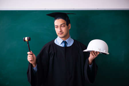 Young male graduate in front of board
