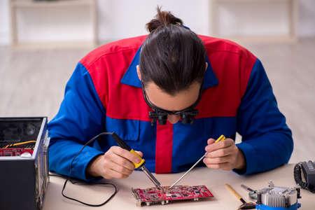 Young male repairman repairing computer Banco de Imagens
