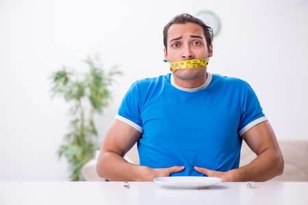 Young hungry man in dieting concept