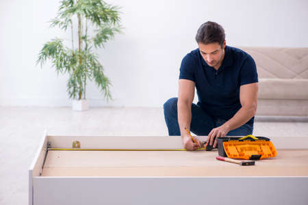 Young male contractor installing furniture at home Banco de Imagens